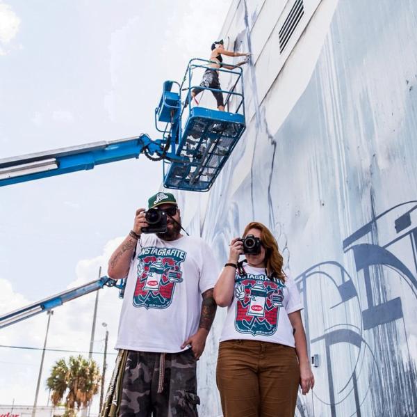 A dupla, brincando de fotógrafos para registrar os artistas 123klan tee e Angelina Cristina em ação em outro mural.