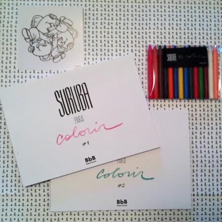 """Detalhe do kit deluxe de """"Suruba Para Colorir"""": dois volumes e uma caixa de giz de cera."""