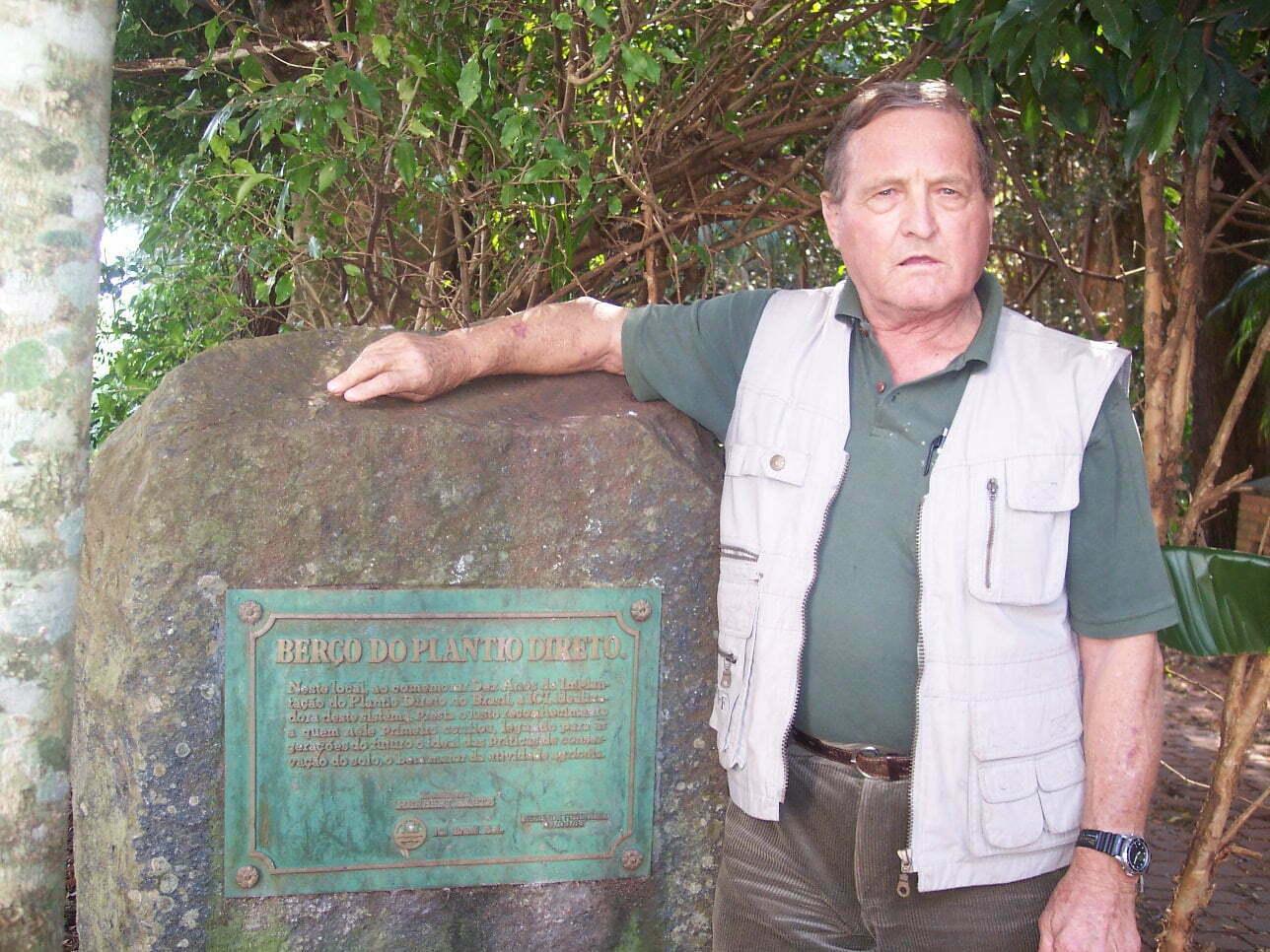 """Herbert Bartz ao lado da placa de 1983 que marcou dez anos de PD no Brasil. No texto, um agradecimento ao primeiro produtor a confiar no sistema, """"legando para as gerações do futuro o ideal das práticas de conservação do solo, o bem maior da atividade agrícola."""""""