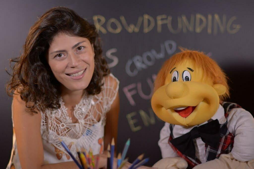 Teacher Camila e o boneco Dedé em ação, durante a videoaula.