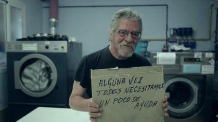 """Francisco segura um papelão com os dizeres """"Algumas vezes, todos precisamos de um pouco de ajuda"""" (foto: Fundação Arrels)."""
