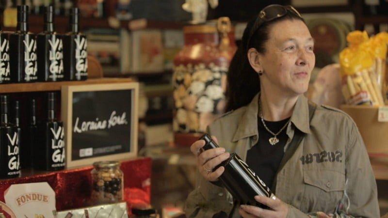 Lorraine, dona da letra que é o maior sucesso de vendas do projeto, segura uma garrafa de azeite da marca gourmet Valonga que leva sua caligrafia (foto: Fundação Arrels).