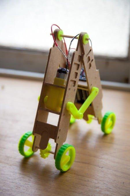 O robôzinho articulado, criado a partir de duas pequenas escadas de madeira, é movido a pilhas.