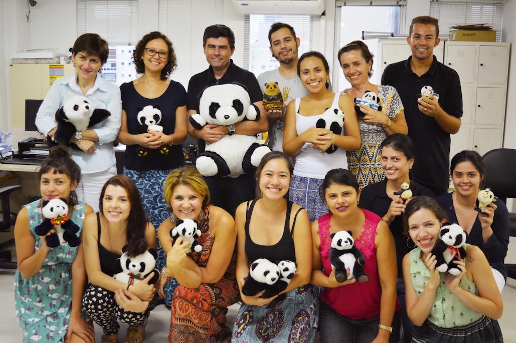 Equipe da Panda Books reunida na sede da editora segurando o mascote da editora.