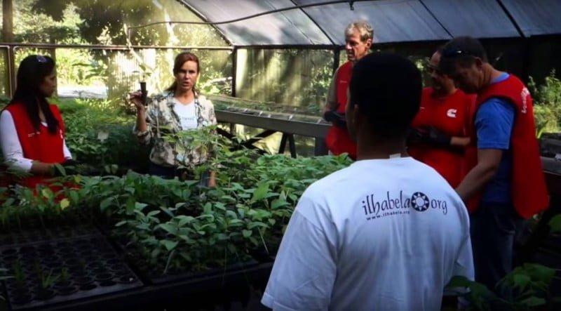 Gisela (ao fundo, segurando uma muda), fala a executivos do curso de cultivo de plantas, ministrado no viveiro da Viva Floresta.