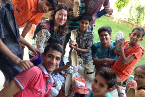 Leticia Sales (ao centro), cercada por garotos indianos que recebem doações de parte do lucro de sua marca de roupa, a Happee.