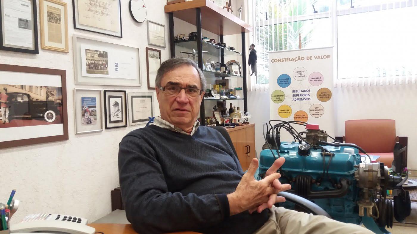 José Carlos Teixeira Moreira em sua sala na Escola de Marketing Industrial, em Cotia (SP). Atrás dele, um motor a diesel igual aos que ele já vendeu.