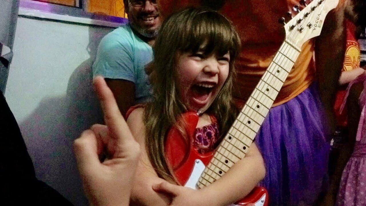 Lucia e sua guitarra, sonho conquistado por meio do site Lâmpada Mágica.