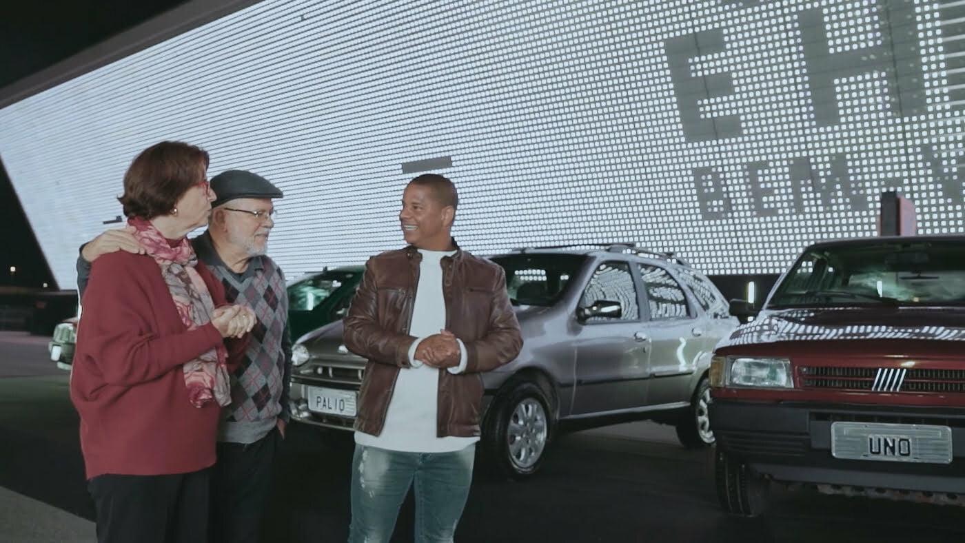 Marcelinho Carioca mostra os carros a dona Suely e seu Hélio.