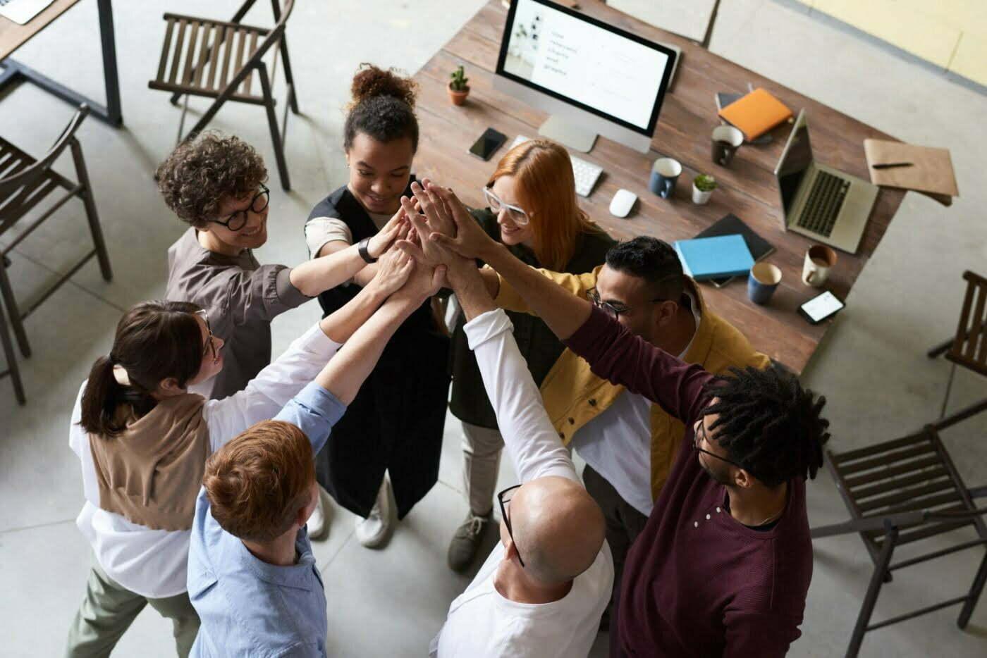 pessoas em uma escritório, dando as mãos, e comemorando