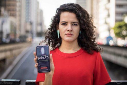 Carolina Oms mostra o Penhas, criado pelo Instituto AzMina. O app pode ser baixado gratuitamente tanto em iOS quanto em Android.